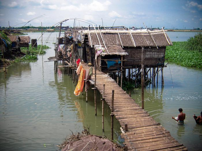 Traditional stilt houses at river bank and connection between man and river