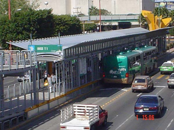 The photo shows an articulated bus docking at a Bus Rapid Transit station in León, Mexico.