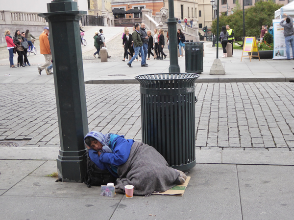 Even in Norway, with very visible government attention and programs, there are an estimated 6200 people with no place to live. Here, in the capital city of Oslo, at the steps of the Parliament Building on the busy avenue connecting the town center with the Royal Palace, a homeless woman tries to sleep and collect a few coins. (Photo by Benjamin Clavan, 2015)