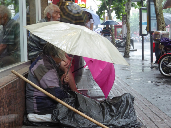 Those without shelter live on the streets as best they can: on this day, trying their best to avoid being soaked by the frequent rain in Shanghai, China while they continue to beg for money.  Photo by Benjamin Clavan, 2015.